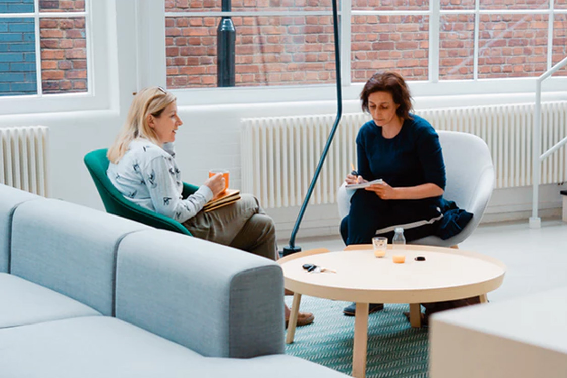 Two women sitting at a coffee table