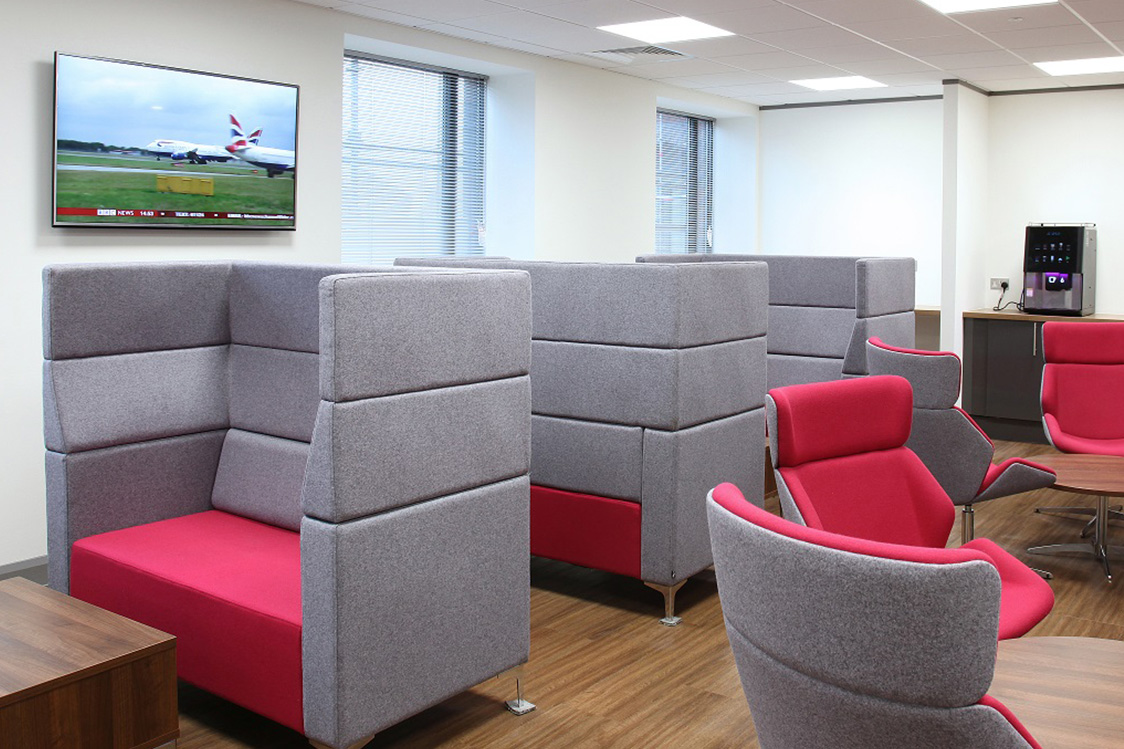 A meeting room consisting of red & grey sofas and wooden coffee tables